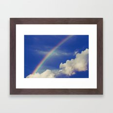 Rainbow over fluffy white clouds in the blue sky Framed Art Print