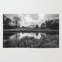 Dramatic sky and reflections on the River Brathay at Elter Water. Lake District, UK. Rug