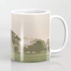 Sunrise burning through heavy fog over countryside scene. Norfolk, UK. Mug