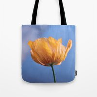 A spring wild yellow flower in blue background. Tote Bag