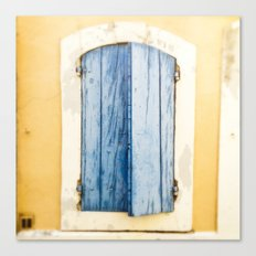 Blue wooden shutter in yellow wall. Canvas Print
