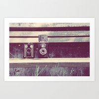 Two Cameras Sitting On A… Art Print