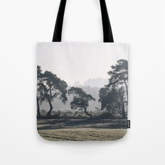 Trees lining a frosty field on a cold morning. Norfolk, UK. Tote Bag