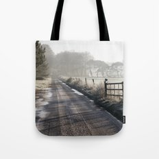 Remote frozen country road a t sunrise. Norfolk, UK. Tote Bag